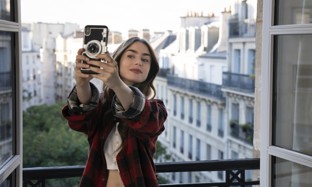 A woman, Emily, stands in front of an opened window, with buildings as a backdrop, taking a selfie with a subtle smile